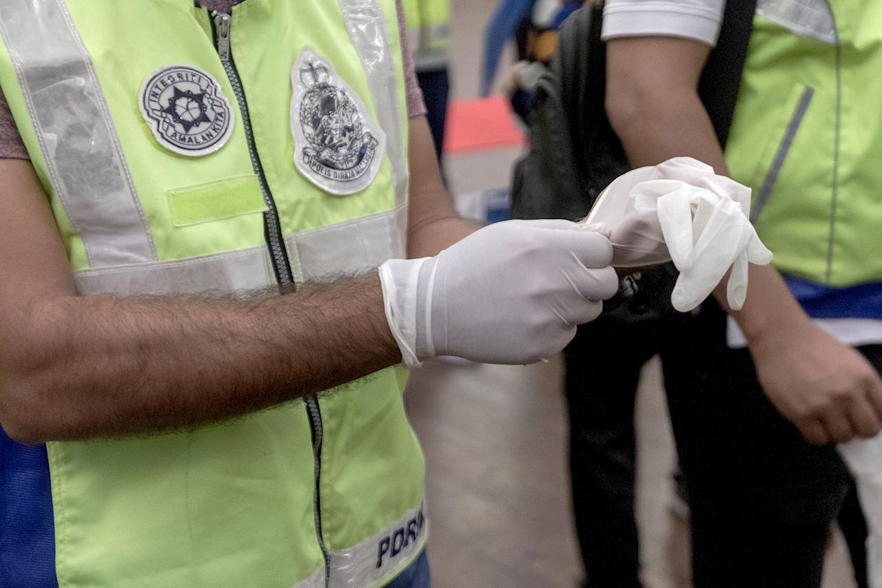 A police officer dons gloves before setting off to enforce Malaysia's Movement Control Order on 18 March 2020. (PHOTO: Fadza Ishak for Yahoo News Singapore)