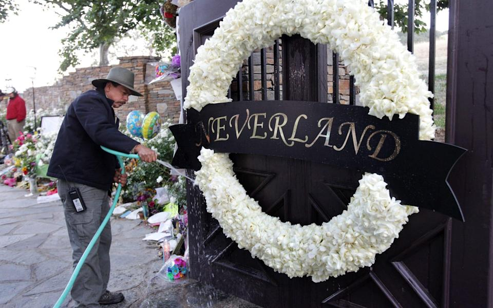 A worker waters thewreath of white roses on the Neverland Ranch gate in 2009 - ap
