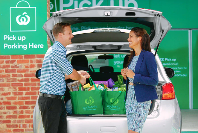 A woman smiling at a Woolworths staff member putting groceries into her car.