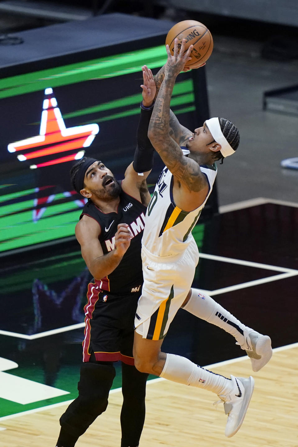 Utah Jazz guard Jordan Clarkson, right, shoots as Miami Heat guard Gabe Vincent defends during the first half of an NBA basketball game, Friday, Feb. 26, 2021, in Miami. (AP Photo/Lynne Sladky)