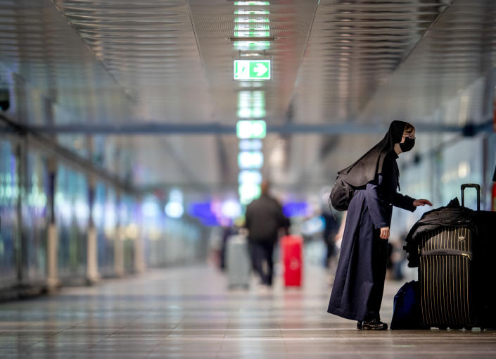A nun wearing a face mask stands next to her baggage at the airport in Frankfurt, Germany, Tuesday, March 30, 2021. (AP Photo/Michael Probst)