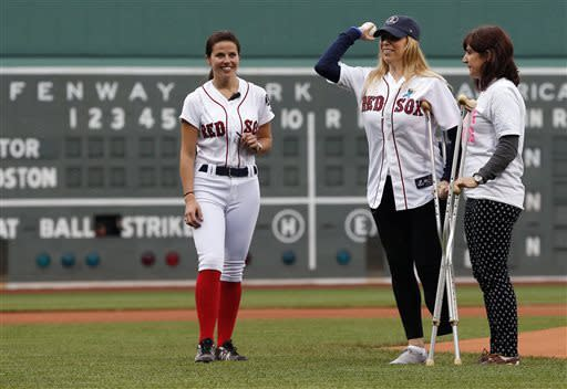 Boston Marathon bombing victim Heather Abbott, center, of Newport, R.I., throws out the ceremonial first pitch before a baseball game between the Boston Red Sox and the Toronto Blue Jays in Boston, Saturday, May 11, 2013. (AP Photo/Michael Dwyer)