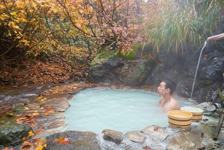 A man sits in a milky pool of hot water underneath autumn foliage.