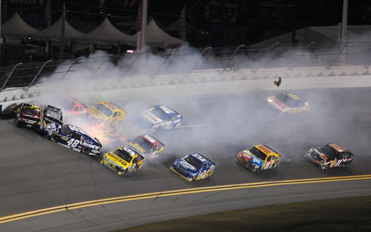 Jeff Gordon, left, slides into the wall as he wrecks with Kurt Busch, second from left, Jimmie Johnson (48) and other drivers during the NASCAR Budweiser Shootout auto race at Daytona International Speedway, Saturday, Feb. 18, 2012, in Daytona Beach, Fla. Kyle Busch (18) won the race. (AP Photo/Phelan M. Ebenhack)