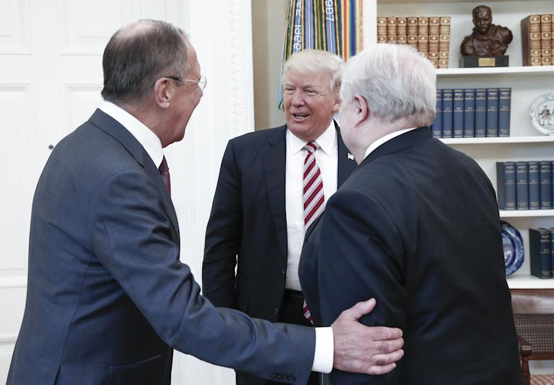 Russia's Foreign Minister Sergei Lavrov, President Donald Trump, and Russian Ambassador to the United States Sergei Kislyak talking during a meeting in the Oval Office.