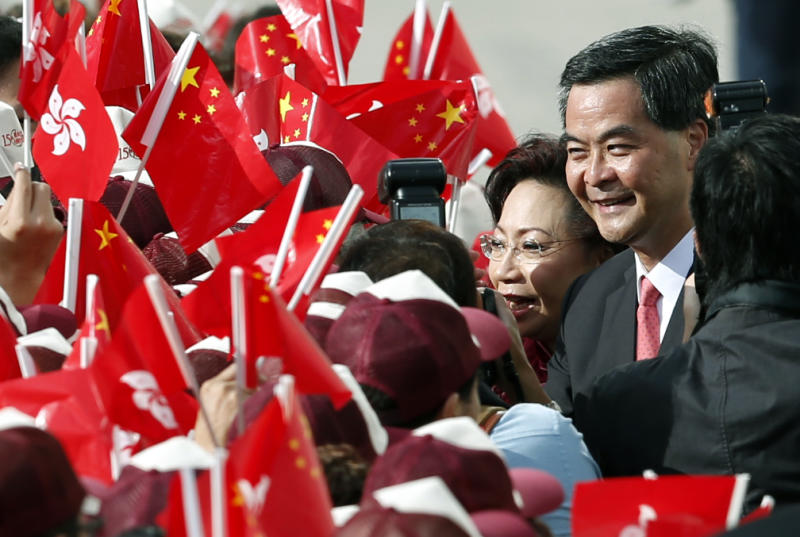 Hong Kong's Chief Executive-elect Leung Chun-ying, right, and his wife Regina shake hands with supporters during a flag raising ceremony to mark the 15th anniversary of Hong Kong's handover to China, Sunday, July 1, 2012, in Hong Kong. Leung was sworn in as Hong Kong's third leader amid growing discontent with China's rule over the Asian financial center. (AP Photo/Kin Cheung)