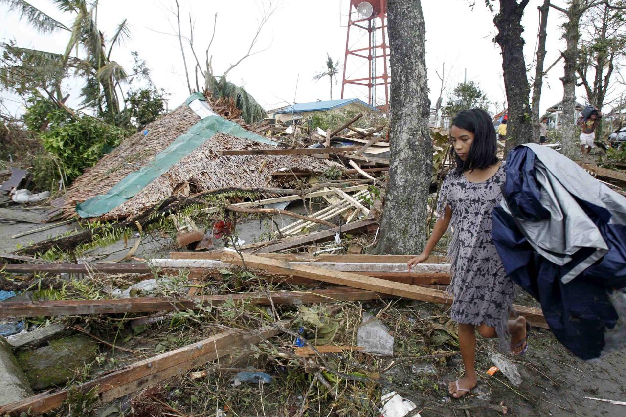 A resident walks past her collapsed house after super Typhoon Haiyan battered Tacloban city, central Philippines, November 9, 2013. Possibly the strongest typhoon ever to hit land devastated the central Philippine city of Tacloban, killing at least 100 people, turning houses into rubble and leveling the airport in a surge of flood water and high wind, officials said on Saturday. The toll of death and damage from Typhoon Haiyan on Friday is expected to rise sharply as rescue workers and soldiers reach areas cut off by the massive, fast-moving storm which weakened to a category 4 on Saturday. REUTERS/Romeo Ranoco (PHILIPPINES - Tags: DISASTER ENVIRONMENT)