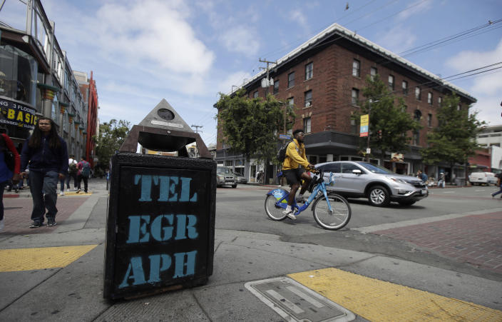 """Traffic and pedestrians cross Telegraph Avenue in Berkeley, Calif., Thursday, July 18, 2019. Soon students in Berkeley, Calif., will have to pledge to """"collegiate Greek system residences"""" instead of sororities or fraternities and city workers will have to refer to manholes as """"maintenance holes."""" Officials in the liberal city this week passed an ordinance to replace some terms with gender-neutral words in the city code. (AP Photo/Jeff Chiu)"""