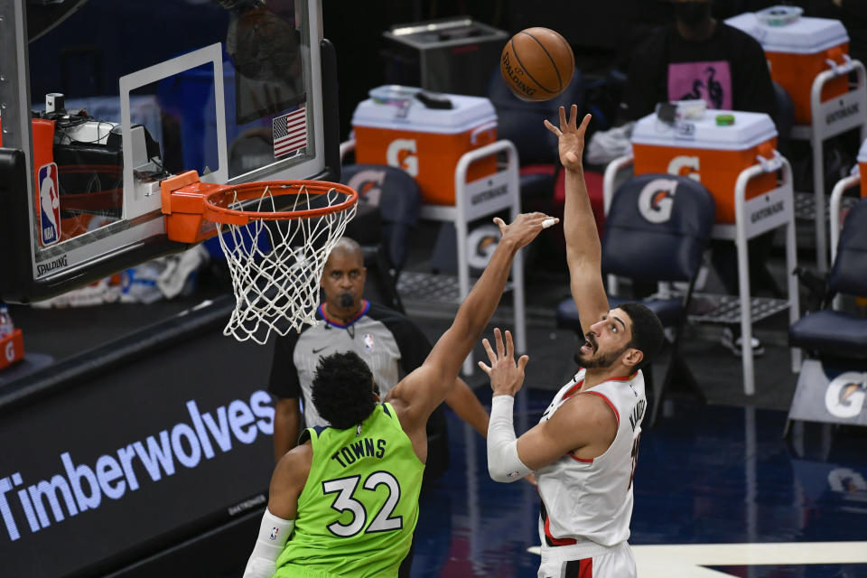 Portland Trail Blazers center Enes Kanter, right, shoots over Minnesota Timberwolves center Karl-Anthony Towns (32) during the first half of an NBA basketball game Saturday, March 13, 2021, in Minneapolis. (AP Photo/Craig Lassig)