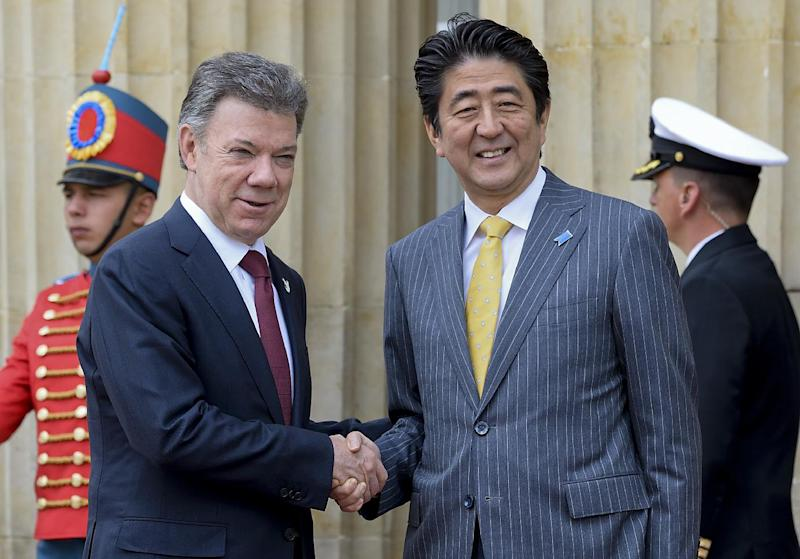 Japan's PM Shinzo Abe (R) and Colombian President Juan Manuel Santos shake hands during the welcoming ceremony at Narino Palace, in Bogota on July 29, 2014
