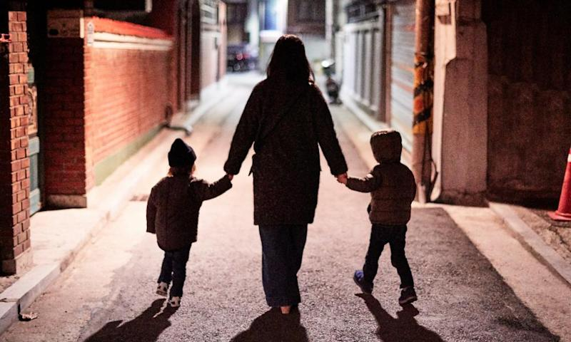 Woman and children walking on street