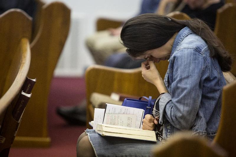 Kathy Abad, a military wife, prays for the victims and families affected by the Fort Hood shooting during a memorial service at the Tabernacle Baptist Church on Sunday, April 6, 2014, in Killeen, Texas. On April 2, 2014, three people were killed and 16 were wounded when a gunman opened fire before taking his own life at the Fort Hood military base. (AP Photo/ Tamir Kalifa)