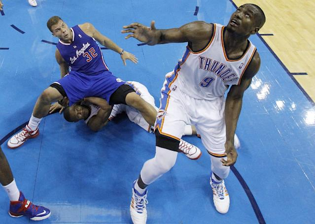 Los Angeles Clippers forward Blake Griffin (32) falls on top of Oklahoma City Thunder guard Russell Westbrook (0) as forward Serge Ibaka (9) watches for a rebound in the third quarter of Game 1 of the Western Conference semifinal NBA basketball playoff series in Oklahoma City, Monday, May 5, 2014. Los Angeles won 122-105. (AP Photo/Sue Ogrocki)