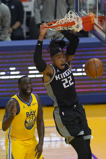 Sacramento Kings forward Richaun Holmes (22) dunks in front of Golden State Warriors forward Draymond Green (23) during the first half of an NBA basketball game in San Francisco, Monday, Jan. 4, 2021. (AP Photo/Jeff Chiu)