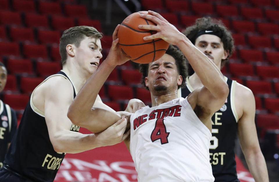 Wake Forest's Jonah Antonio (20) fouls North Carolina State's Jericole Hellems (4) during the first half of an NCAA college basketball game Wednesday, Jan. 27, 2021, in Raleigh, N.C. (Ethan Hyman/The News & Observer via AP, Pool)