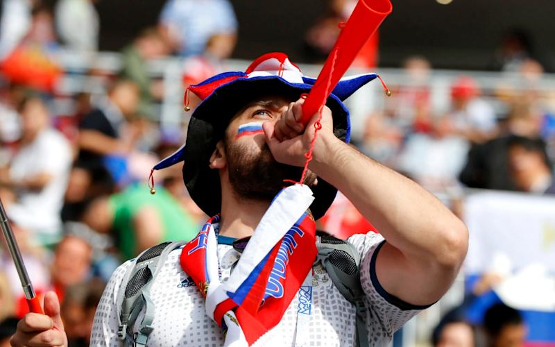 A Russian fan bangs the drum, by blowing a horn, for his team - Getty Images Europe