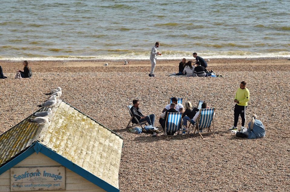 """People observe social distancing on the beach  in Brighton, southern England, on May 16, 2020, following an easing of lockdown rules in England during the novel coronavirus COVID-19 pandemic. - People are being asked to """"think carefully"""" before visiting national parks and beaches on the first weekend since coronavirus lockdown measures were partially eased in England. (Photo by Glyn KIRK / AFP) (Photo by GLYN KIRK/AFP via Getty Images)"""