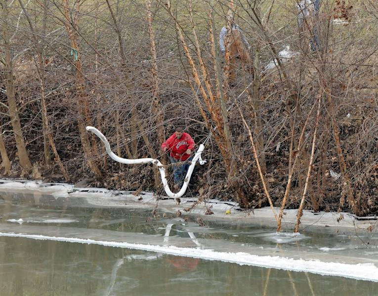 A Freedom Industries worker places a boom in the Elk River Thursday, Jan. 9, 2014, at the site of a chemical leak in Charleston that has fouled the drinking water in five West Virginia counties. (AP Photo/The Charleston Gazette, Chris Dorst)