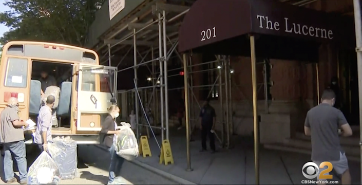 People carry their belongings into the Lucerne Hotel in Manhattan's Upper West Side: Screengrab / CBS
