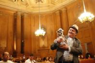 """Dog owner Dean Clark presents Frida, a female Chihuahua, as the San Francisco Board of Supervisors issues a special commendation naming Frida """"Mayor of San Francisco for a Day"""" in San Francisco, California November 18, 2014. REUTERS/Stephen Lam"""