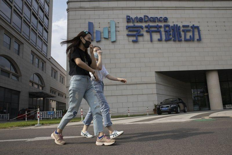 FILE - In this Aug. 7, 2020, file photo, women wearing masks to prevent the spread of the coronavirus chat as they pass by the headquarters of ByteDance, owners of TikTok, in Beijing, China. TikTok's owner said Thursday, Sept. 24, 2020, that it has applied for a Chinese technology export license as it tries to complete a deal with Oracle and Walmart to keep the popular video app operating in the United States.