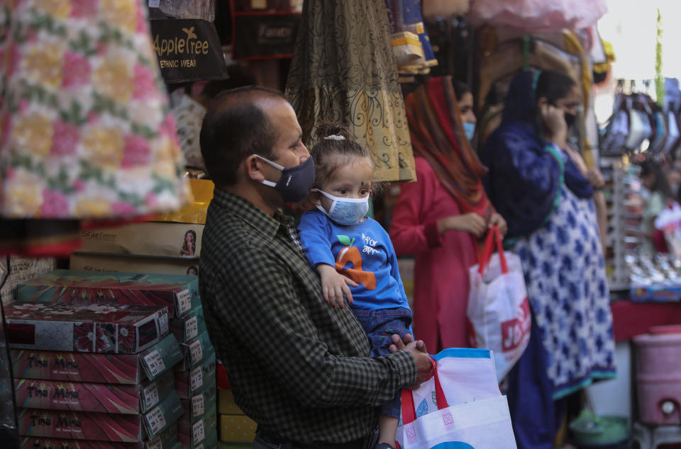 A man carries a child, both wearing masks as a precaution against the coronavirus as he shops at a market ahead of Hindu festivals in Jammu, India, Thursday, Oct.29, 2020. India's confirmed coronavirus caseload surpassed 8 million on Thursday with daily infections dipping to the lowest level this week, as concerns grew over a major Hindu festival season and winter setting in. (AP Photo/Channi Anand)