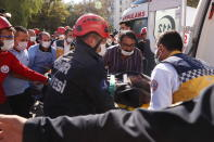 Medics and rescue personnel carry into an ambulance an injured person from the debris of a collapsed building in Izmir, Turkey, Saturday, Oct. 31, 2020. Rescue teams on Saturday ploughed through concrete blocs and debris of eight collapsed buildings in Turkey's third largest city in search of survivors of a powerful earthquake that struck Turkey's Aegean coast and north of the Greek island of Samos, killing dozens Hundreds of others were injured. (AP Photo/Darko Bandic)
