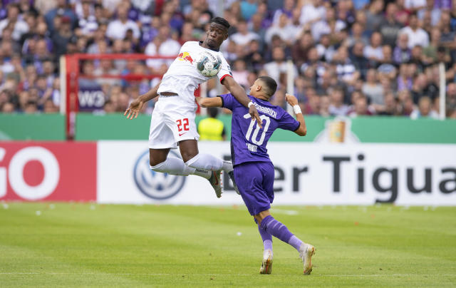 Leipzig's Nordi Mukiele, left, challenges for the ball with Osnabrueck's Anas Quahim, right, during the German soccer cup, DFB Pokal, first Round match between VfL Osnabrueck - RB Leipzig in Osnabrueck, Sunday, Aug. 11, 2019. (Guido Kirchner/dpa via AP)