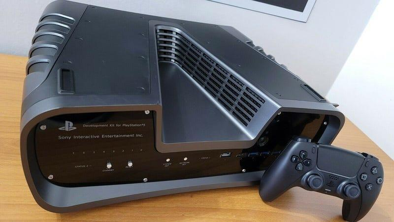 A V-shaped PlayStation 5 dev set sits on a wooden table.