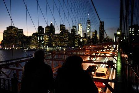People watch passing traffic below as they stand on the Brooklyn Bridge over the East River between the boroughs of Brooklyn and Manhattan in New York City