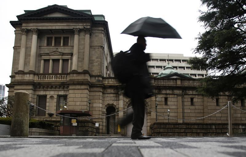 A pedestrian holding an umbrella to take shelter from rain and hail walks past the Bank of Japan headquarters building in Tokyo