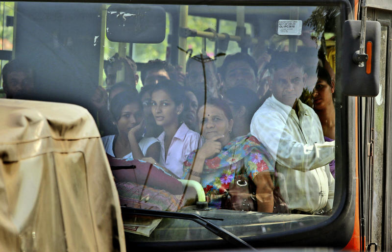 Indian passengers riding on a public bus look towards a court complex crowded with media personnel awaiting a verdict in the Dec. 16, 2012 gang rape case, in New Delhi, India, Tuesday, Sept. 10, 2013. The Indian court is set to deliver judgment in the fatal gang rape of a young woman on a moving New Delhi bus last year that has incensed the public and fueled debate over whether women can be safe in India. (AP Photo/Manish Swarup)