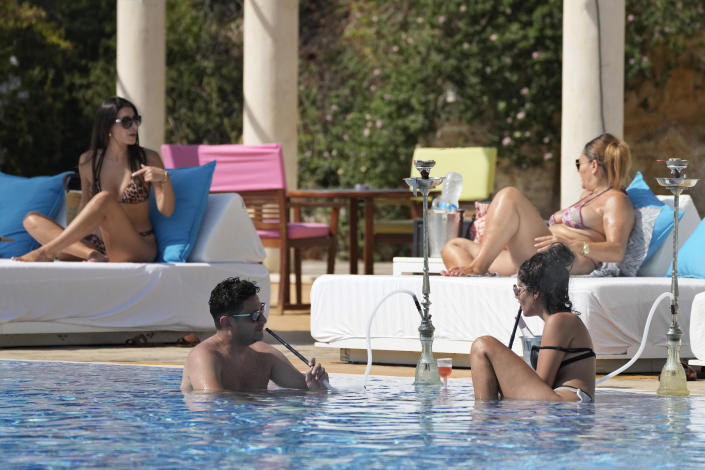 """A couple smoke a traditional """"shisha"""" water pipe as they sit in a swimming pool at the Edde Sands beach resort in the ancient Phoenician city of Byblos north of Beirut, Lebanon, Friday, July 2, 2021. With their dollars trapped in the bank, a lack of functioning credit cards and travel restrictions imposed because of the pandemic, many Lebanese who traditionally vacationed over the summer at regional hotspots are also now turning toward domestic tourism. (AP Photo/Hassan Ammar)"""