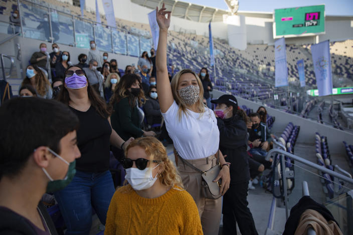 """Audience members wear protective face masks during a performance of Israeli musician Ivri Lider at a soccer stadium in Tel Aviv, Friday, March. 5, 2021. All guests were required to show """"green passport"""" proof of receiving a COVID-19 vaccination or full recovery from the virus. (AP Photo/Oded Balilty)"""