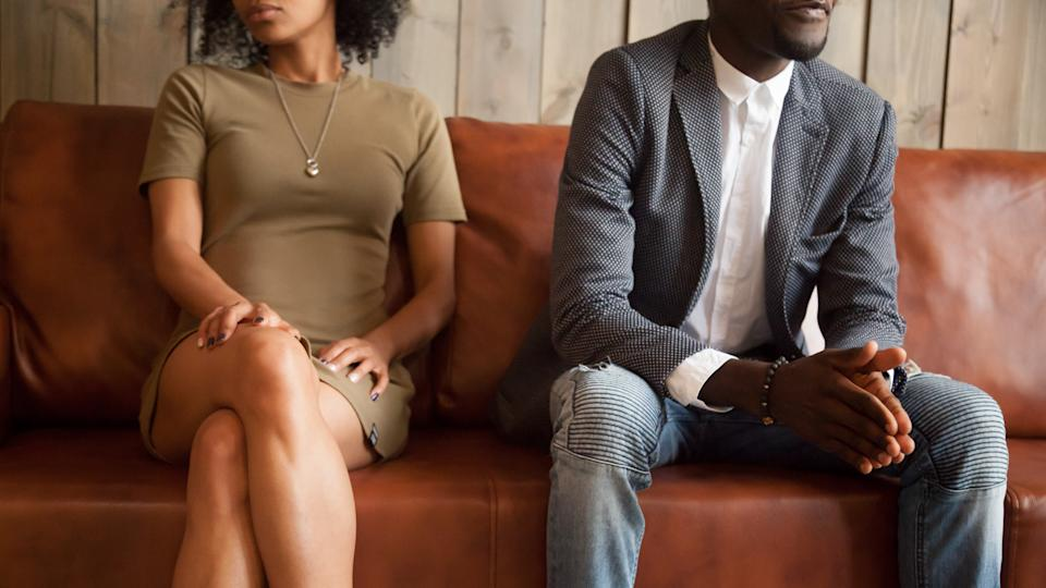African american unhappy couple sitting on couch after quarrel fight thinking of break up or divorce, black upset man and woman not talking having conflict, bad relationships concept, close up view.