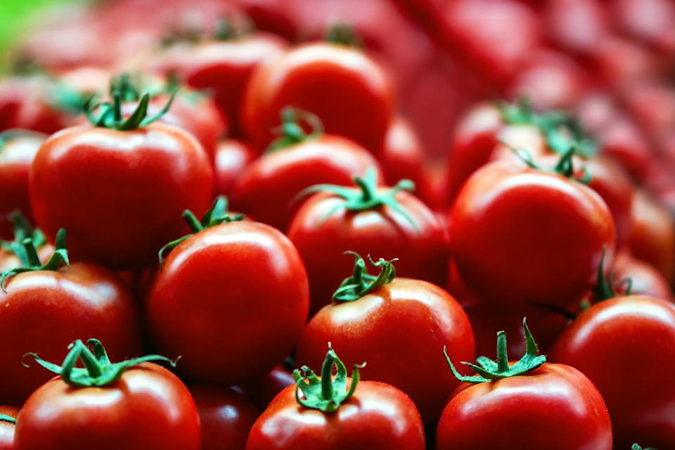 Lots of red fresh ripe tomatoes close up in the supermarket. Vegetables harvest. Food natural background