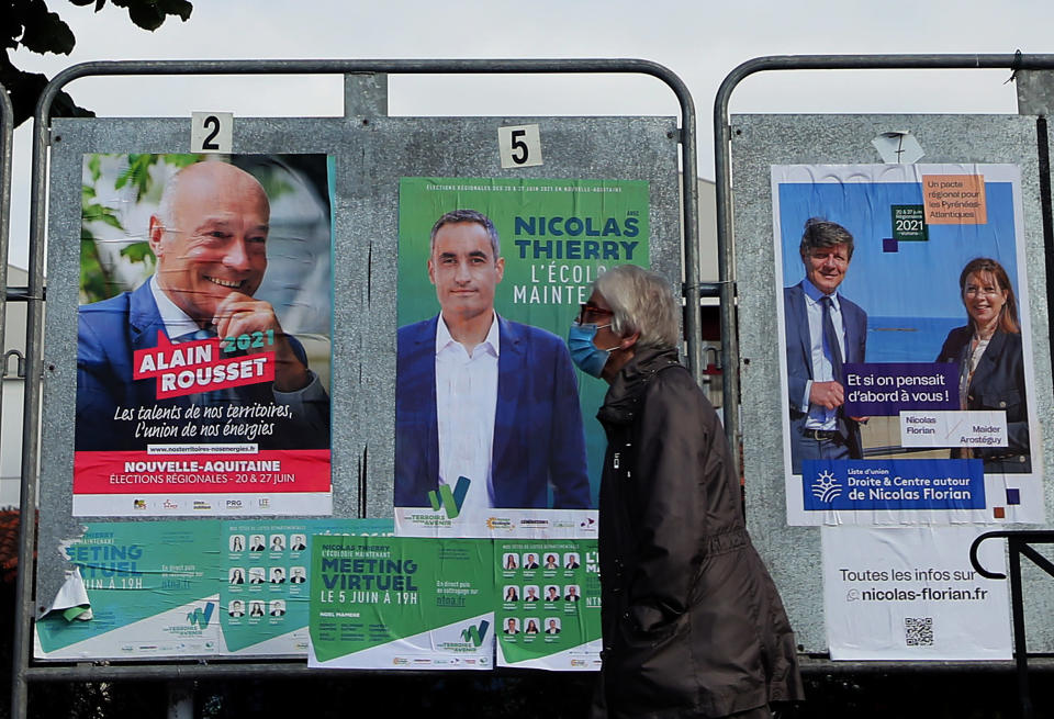 A woman walks past election campaign posters advertising the upcoming regional election in Saint Jean de Luz, southwestern France, Friday, June 25, 2021. The second round of French local elections will be held on June 27. (AP Photo/Bob Edme)