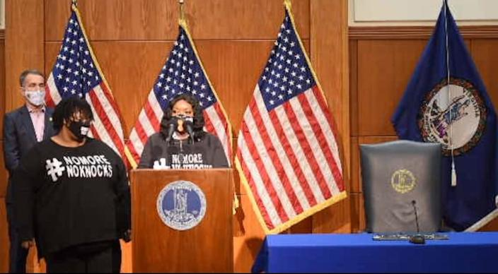 Bianca Austin, at podium, speaks on the ban of no-knock search warrants in Virginia during a bill-signing ceremony in Richmond, Va. Monday, Dec. 7, 2020. Joining her are Gov. Ralph S. Northan, left, and Austin's sister, Tahasha Holloway.