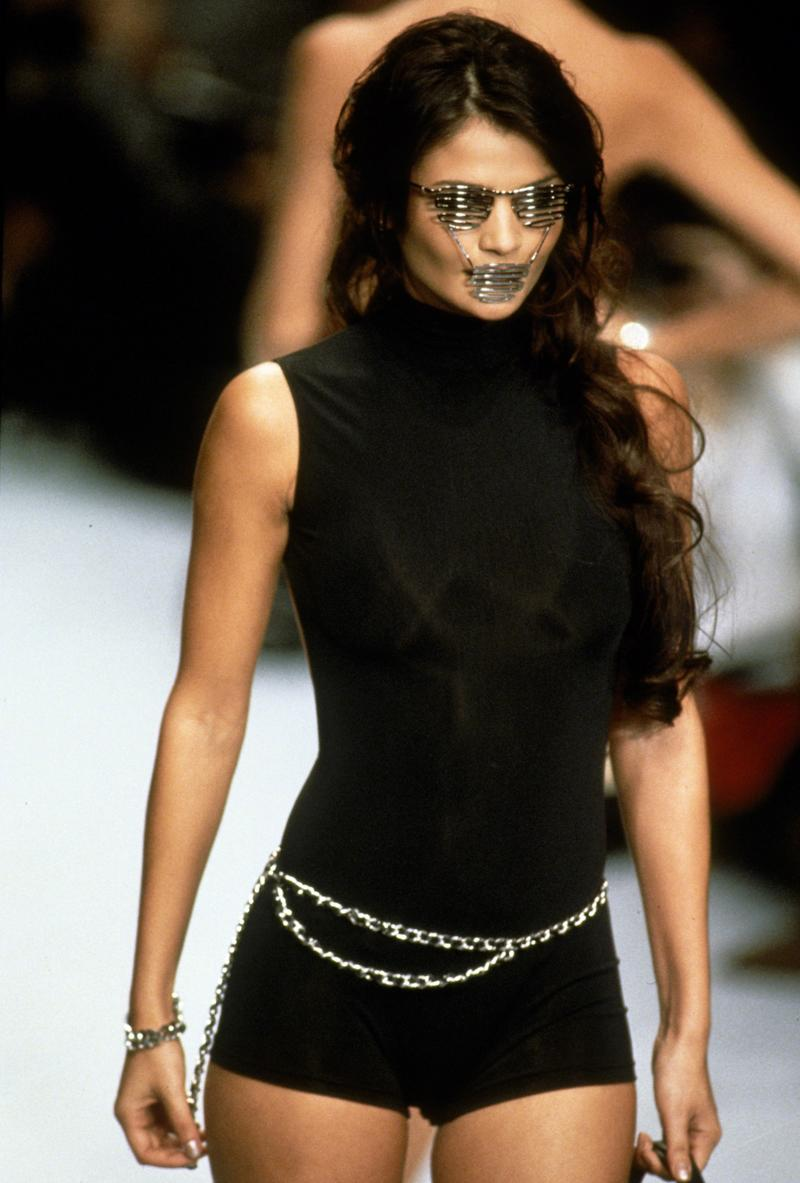 The '90s marked the height of Lagerfeld's experiments with many of the most storied Hallmarks of Chanel, including the house's classic chains. It wasn't Helena Christensen's belted waist or short shorts, though, that caught the eye during the house's spring/summer 1996 show, but instead the proto-shutter shades she wore that came complete with a muzzle-like extension for her mouth.