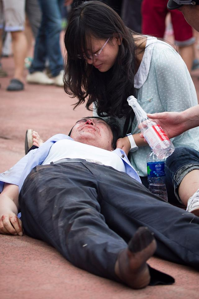SHANGHAI, CHINA - JUNE 20: (CHINA OUT)  An injured police officer receives assistance after being caught in a crush of people as David Beckham arrived at Tongji University on June 20, 2013 in Shanghai, China. The stampede is reported to have left five people injured and hospitalised. (Photo by Getty Images)