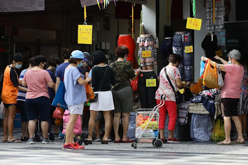 SINGAPORE - JULY 07: People shop for pants on sale without observing social distancing on July 7, 2020 in Singapore. As of July 7, Singapore reported 157 of coronavirus (COVID-19) infections, seeing an increase in the average number of COVID-19 infections within the community after the country lifted its partial lockdown. The total number of COVID-19 cases in the country stands at 45,140. (Photo by Suhaimi Abdullah/Getty Images)