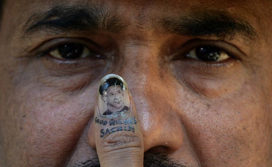 Indian artist Ramesh Sah displays a miniature portrait of Indian cricketer Sachin Tendulkar he painted onto his thumbnail in Siliguri on November 16, 2013. AFP PHOTO / Diptendu DUTTA