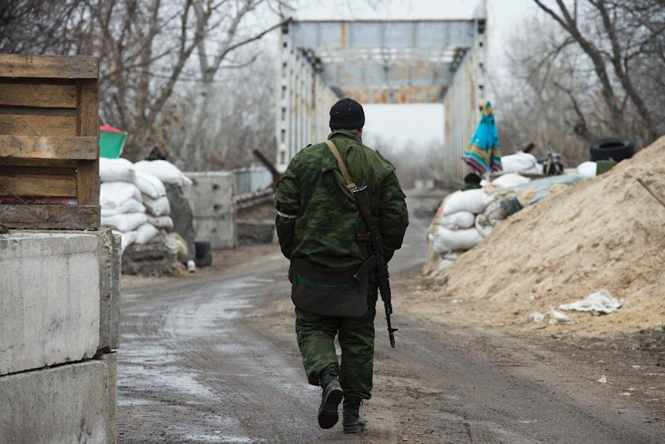 A member of a Cossack unit aligned with the self-proclaimed Luhansk People's Republic walks at a checkpoint near a bridge over the river Donets just north of Luhansk March 13, 2015 (AFP Photo/John Macdougall)