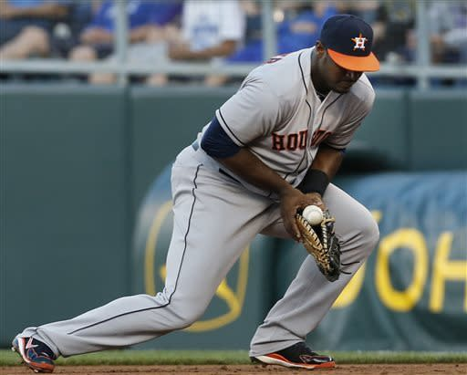Houston Astros left fielder Chris Carter handles a ground ball hit by Kansas City Royals' Chris Getz during the third inning a baseball game at Kauffman Stadium in Kansas City, Mo., Friday, June 7, 2013. Getz was forced out at first base on the play. (AP Photo/Orlin Wagner)