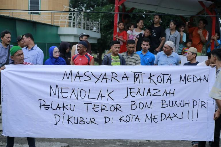 Indonesian residents hold a banner that reads 'residents of Medan city reject the body of suicide bomber to be burried in Medan city'