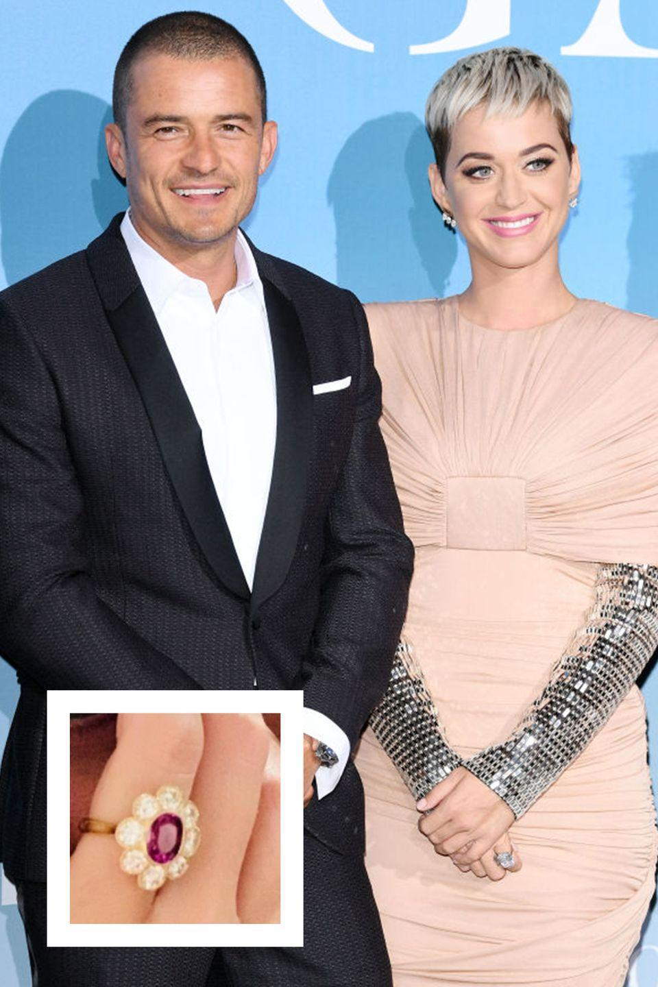 """<p>Katy announced her engagement to Orlando Bloom with a sweet Instagram post on Valentine's Day. The actor proposed <a href=""""https://www.townandcountrymag.com/style/jewelry-and-watches/a26360336/katy-perry-engagement-ring-worth-cost-details/"""" rel=""""nofollow noopener"""" target=""""_blank"""" data-ylk=""""slk:with a one-of-a-kind sparkler"""" class=""""link rapid-noclick-resp"""">with a one-of-a-kind sparkler</a> featuring a ruby or vivid pink diamond center stone weighing between two to two and a half carats in size. The overall cost of the ring may range between $500,000 and $2,000,000 (or even more!). </p>"""