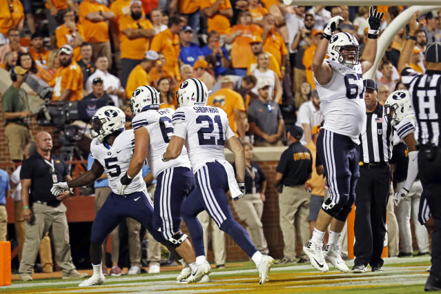 Brigham Young running back Ty'Son Williams (5) celebrates the game-winning touchdown with teammates in overtime an NCAA college football game Saturday, Sept. 7, 2019, in Knoxville, Tenn. Brigham Young won 29-26. (AP Photo/Wade Payne)