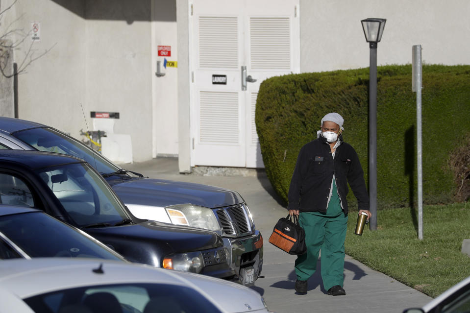 A health care worker leaves Cedar Mountain Post Acute nursing facility in Yucaipa, Calif., Wednesday, April 1, 2020. The Southern California nursing home has been hit hard by the coronavirus, with more than 50 residents infected, a troubling development amid cautious optimism that cases in the state may peak more slowly than expected. (AP Photo/Chris Carlson)