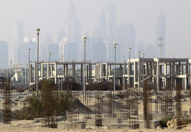With the city skyline in the background, an unfinished construction site of Jumeirah Village, which has been left the same since the 2009 financial crisis, is seen in Dubai, United Arab Emirates, Tuesday, Oct. 8, 2013. A hunger strike started in September by a few prisoners, convicted under the strict financial codes of the United Arab Emirates, has now grown to more than 50 people demanding authorities reconsider their sentences that can bring years behind bars for a single bounced check. (AP Photo/Kamran Jebreili)