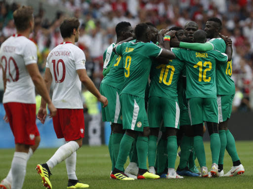 Senegal's Idrissa Gana Guey celebrates with teammates after scoring the opening goal during the group H match between Poland and Senegal at the 2018 soccer World Cup in the Spartak Stadium in Moscow, Russia, Tuesday, June 19, 2018. (AP Photo/Darko Vojinovic)